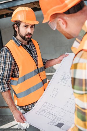 builders with blueprint having conversation at construction site