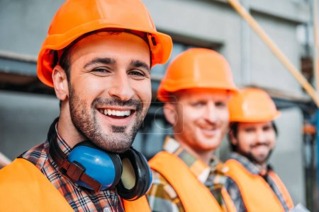 Photo pour Gros plan tiré du groupe de constructeurs équipés en regardant la caméra sur le chantier - image libre de droit