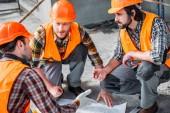 Close-up foto de grupo de constructores seguros de conversación sobre la construcción de plan