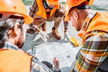 close-up shot of group of builders in hard hats having conversation about building plan