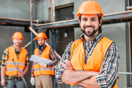 handsome smiling builder standing at construction site with crossed arms while his colleagues standing blurred on background
