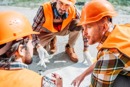 close-up shot of group of builders in hard hats having conversation about blueprint