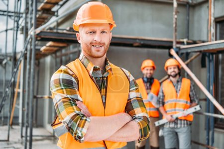 smiling builder standing at construction site with crossed arms while his colleagues standing blurred on background