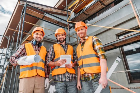 bottom view of group of smiling builders with blueprint and tablet looking at camera at construction site