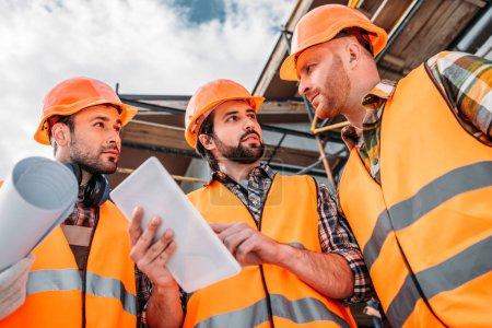 Foto de Grupo de constructores con tableta digital en el sitio de construcción - Imagen libre de derechos