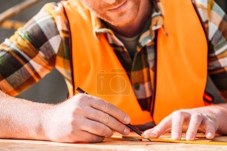 cropped shot of builder using measuring tape and pencil