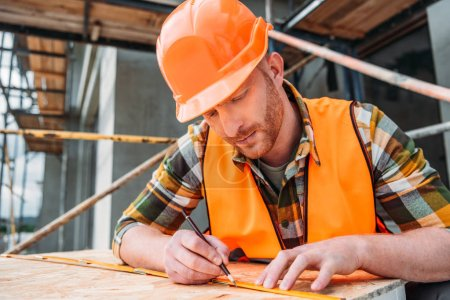 handsome builder using measuring tape and pencil at construction site