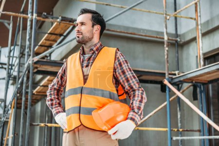 handsome builder in reflective vest holding helmet while standing in front of building house and looking away