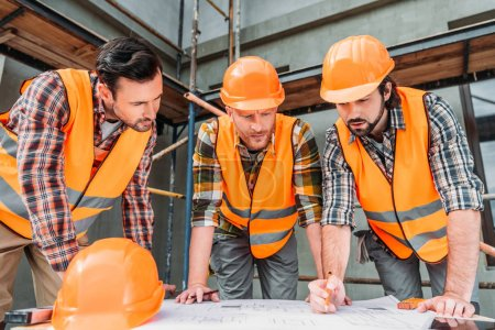 group of confident builders looking at building plan at construction site