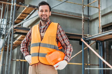 Photo for Happy builder in reflective vest holding helmet while standing in front of building house and looking at camera - Royalty Free Image