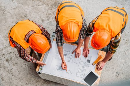 high angle view of group of builders discussing building plan at construction site