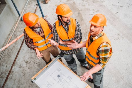 high angle view of group of confused builders discussing building plan at construction site