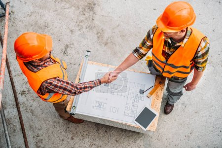 high angle view of builders shaking hands over blueprint at construction site