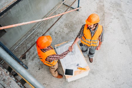 Photo for High angle view of builders shaking hands at construction site - Royalty Free Image