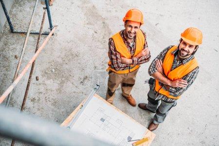 Photo pour Vue d'angle élevé des constructeurs souriants avec blueprint permanent sur le chantier et regardant la caméra - image libre de droit
