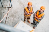 high angle view of smiling builders with blueprint standing at construction site and looking at camera