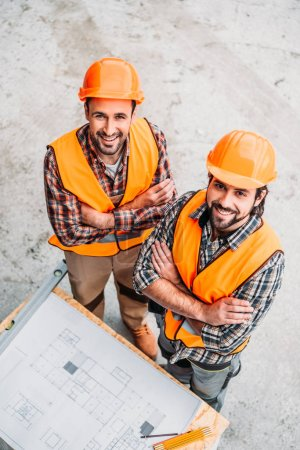 high angle view of happy builders with blueprint standing at construction site and looking at camera