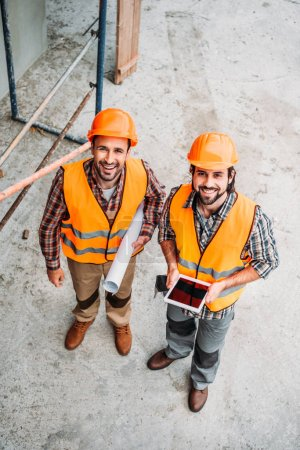 Photo pour Vue de la forte inclinaison des constructeurs avec blueprint et tablette debout sur le chantier et en regardant la caméra - image libre de droit