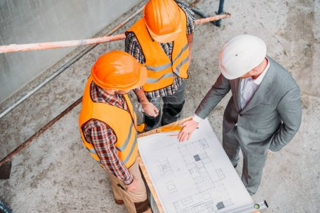 Photo for High angle view of builders and architect discussing blueprint at construction site - Royalty Free Image