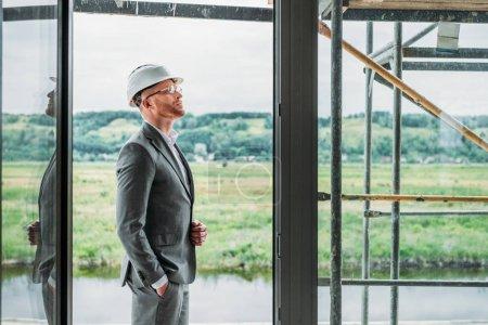Photo pour Vue de côté d'architecte beau costume et permanente d'un casque sur la terrasse au chantier de construction - image libre de droit