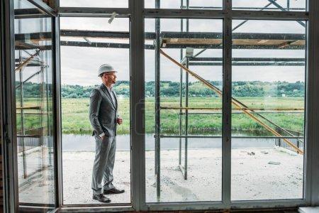 Photo pour Architecte beau costume et casque se tenant debout sur terrasse sur chantier - image libre de droit