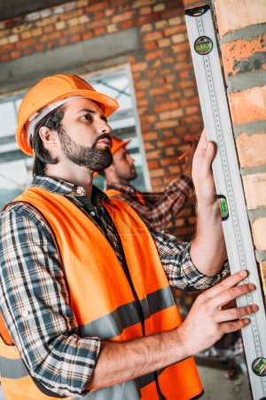 Photo pour Vue latérale du beau constructeur à l'aide du niveau à bulle sur chantier et son collègue travaillant sur fond - image libre de droit