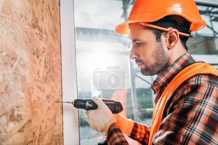 side view of handsome builder using handheld electric drill