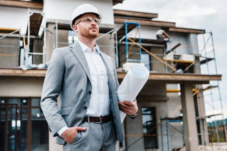 handsome architect in suit and hard hat holding blueprint standing in front of building house and looking away