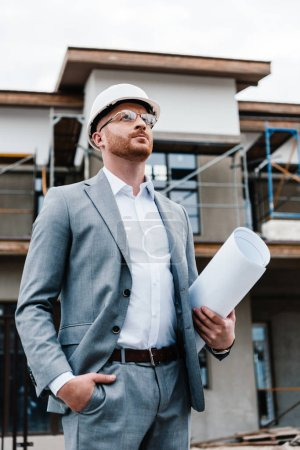 handsome architect in suit and hard hat holding blueprint standing in front of building house
