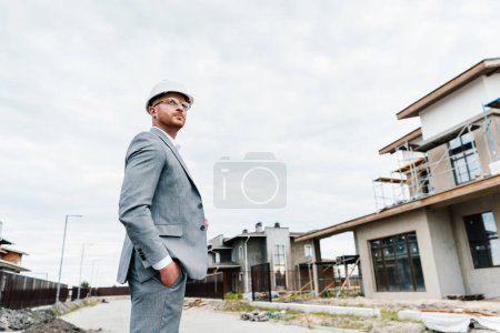 successful architect in suit and hard hat standing in front of building house