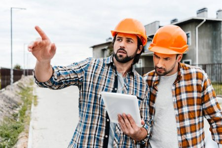 architects using digital tablet and pointing somewhere