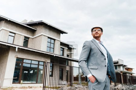 handsome architect in suit and hard hat standing in front of building house