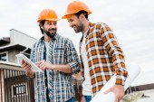 architects with blueprint and tablet working together at construction site