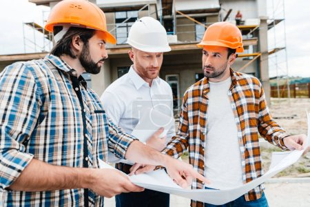 group of architects with building plan having conversation in front of construction site