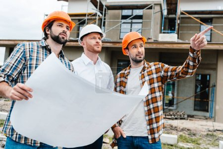 group of architects with building plan standing in front of construction site and looking away