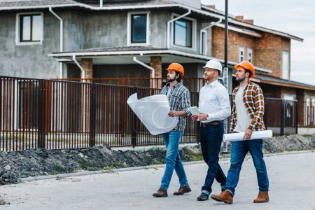 group of architects walking by building street with blueprints