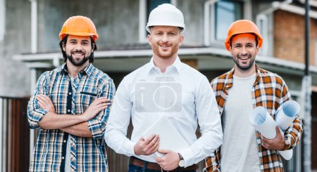 group of successful architects in hard hats looking at camera in front of building house