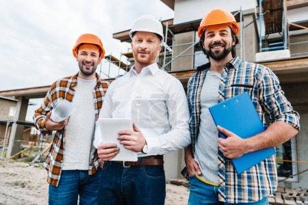 Foto de Grupo de arquitectos sonrientes en cascos, mirando a cámara frente a la casa del edificio - Imagen libre de derechos
