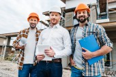 group of smiling architects in hard hats looking at camera in front of building house