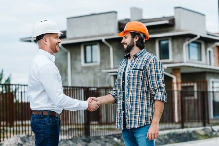 handsome architects shaking hands at construction site