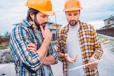 confident architects using digital tablet at construction site