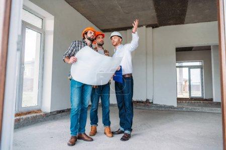 Foto de Grupo de arquitectos con blueprint tener conversación y mirando lejos dentro de la construcción edificio - Imagen libre de derechos