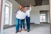 Grupo de arquitectos con blueprint tener conversación y mirando lejos dentro de la construcción edificio