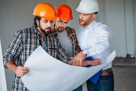 group of adult architects with blueprint having conversation inside of constructing building