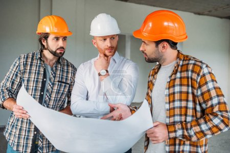 group of handsome architects with blueprint having conversation inside of constructing building