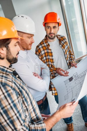 Photo for Group of architects with blueprint having conversation inside of constructing building - Royalty Free Image
