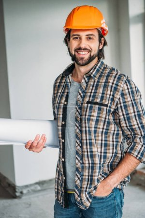 successful smiling architect in plaid shirt and hard hat standing inside of building house with blueprint and looking at camera