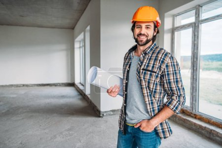 handsome smiling architect in plaid shirt and hard hat standing inside of building house with blueprint and looking at camera