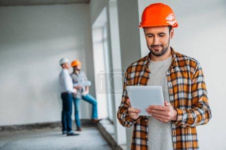 Photo pour Beau architecte en chemise à carreaux et un casque permanent à l'intérieur de la maison de construction et à l'aide de tablette - image libre de droit