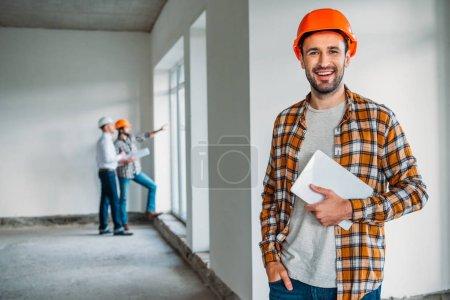 Photo pour Bel architecte en chemise à carreaux et chapeau dur debout à l'intérieur de la maison de construction avec tablette dans les mains - image libre de droit